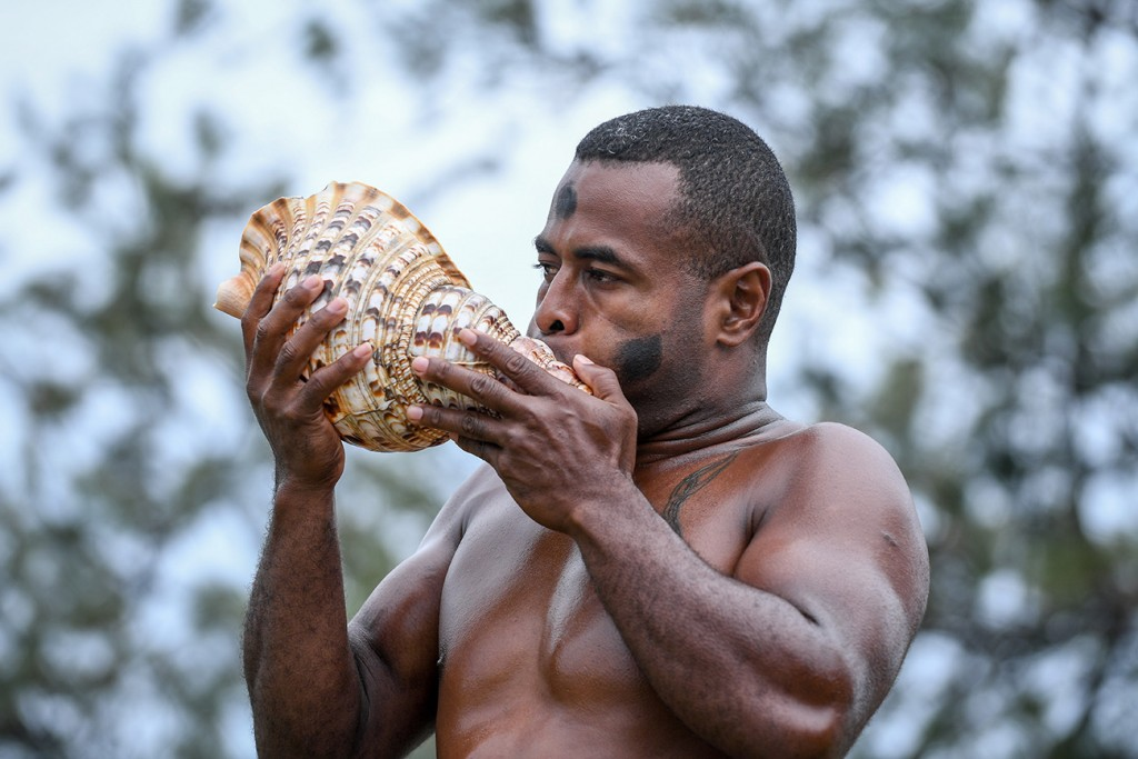 A traditional Fiji warrior blows a shell horn to announce the arrival of the bride