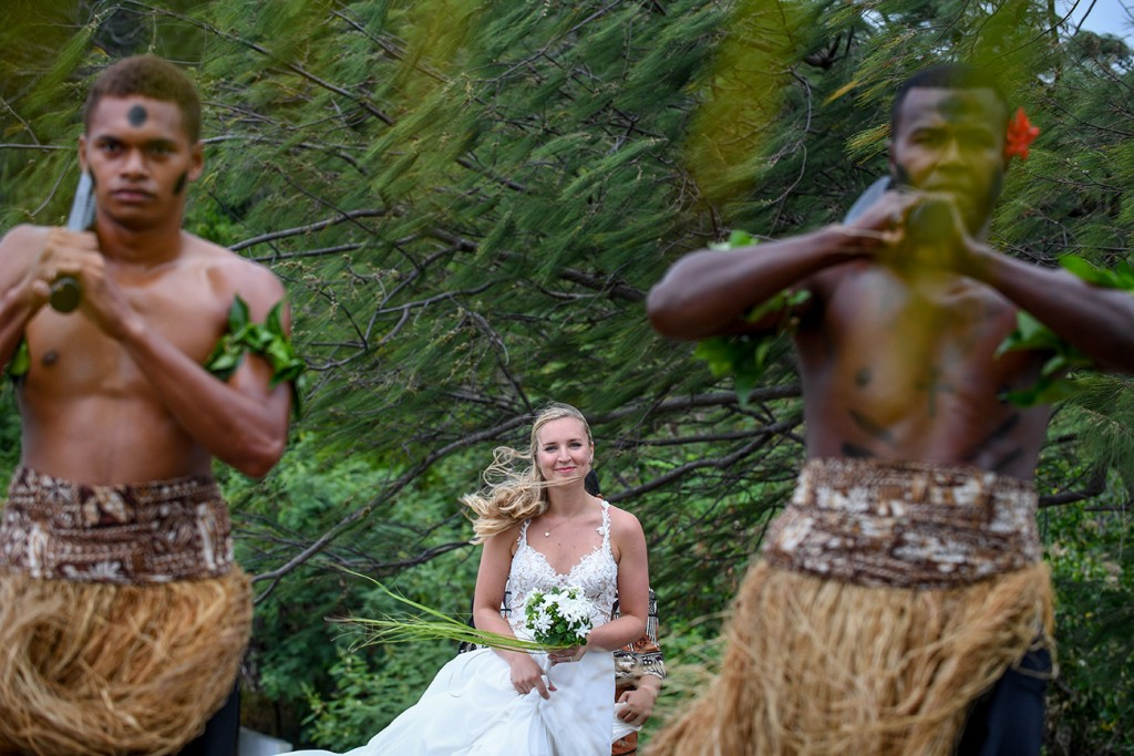 The bride walks down the aisle led by traditional Fiji warriors