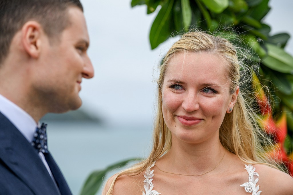 A tearful bride smiles at her groom