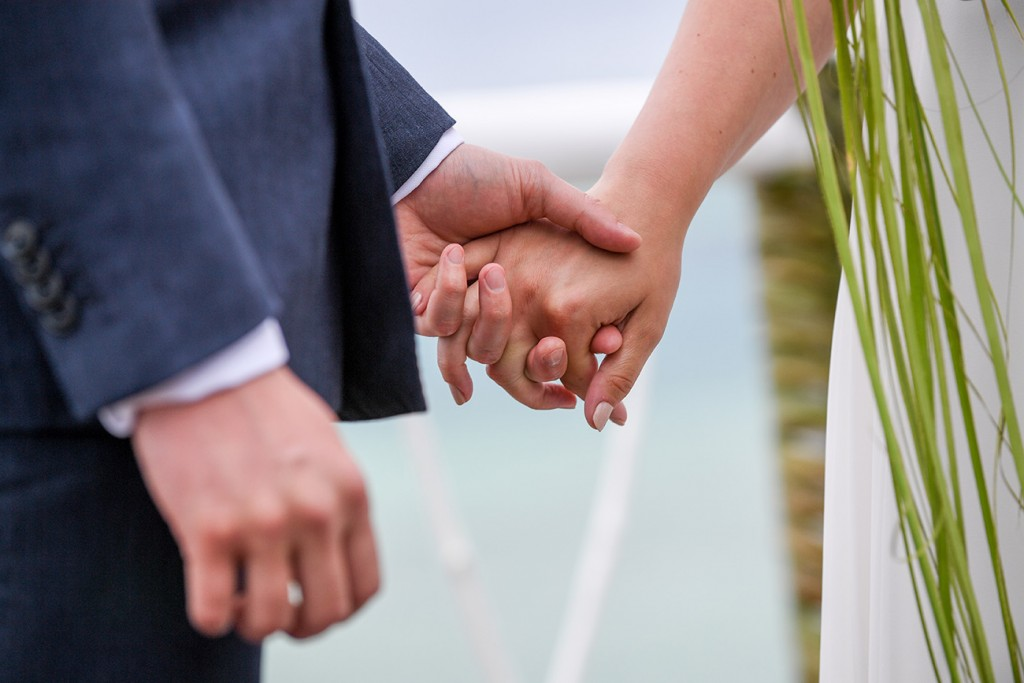 The married couple hold hands at the altar