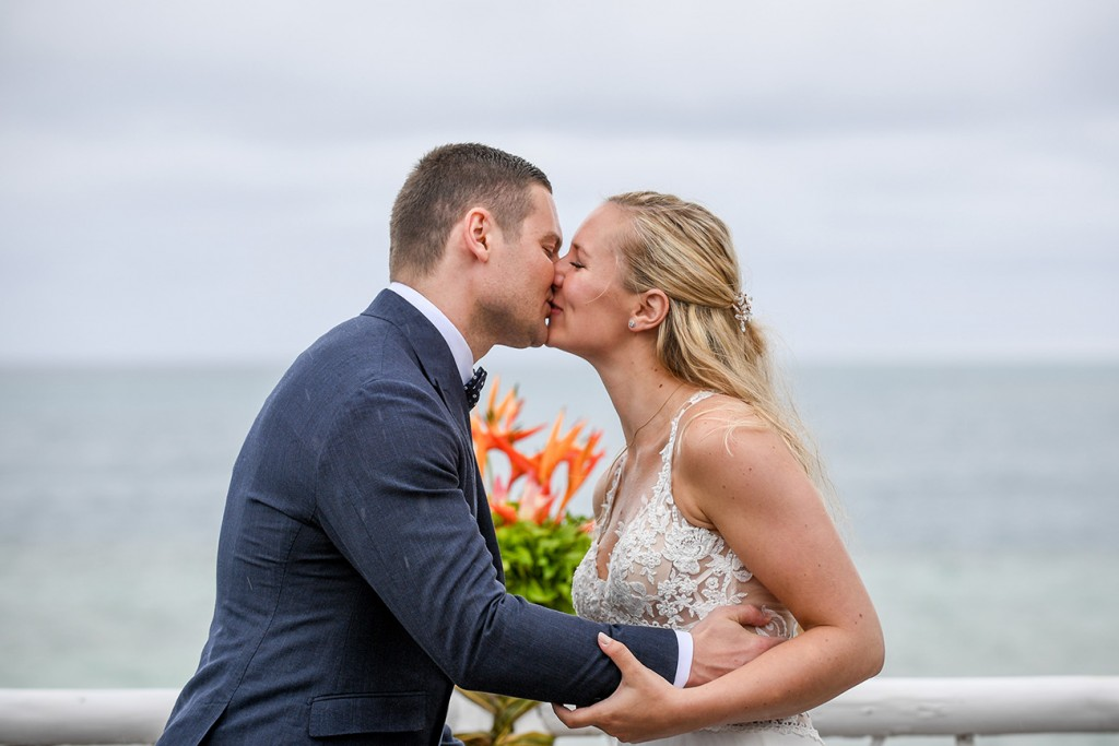 The newly weds kiss overlooking the Pacific Ocean
