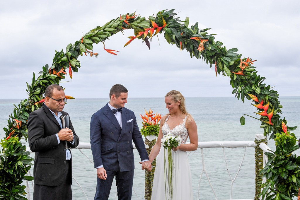 The newly weds hold hands at the beach view altar