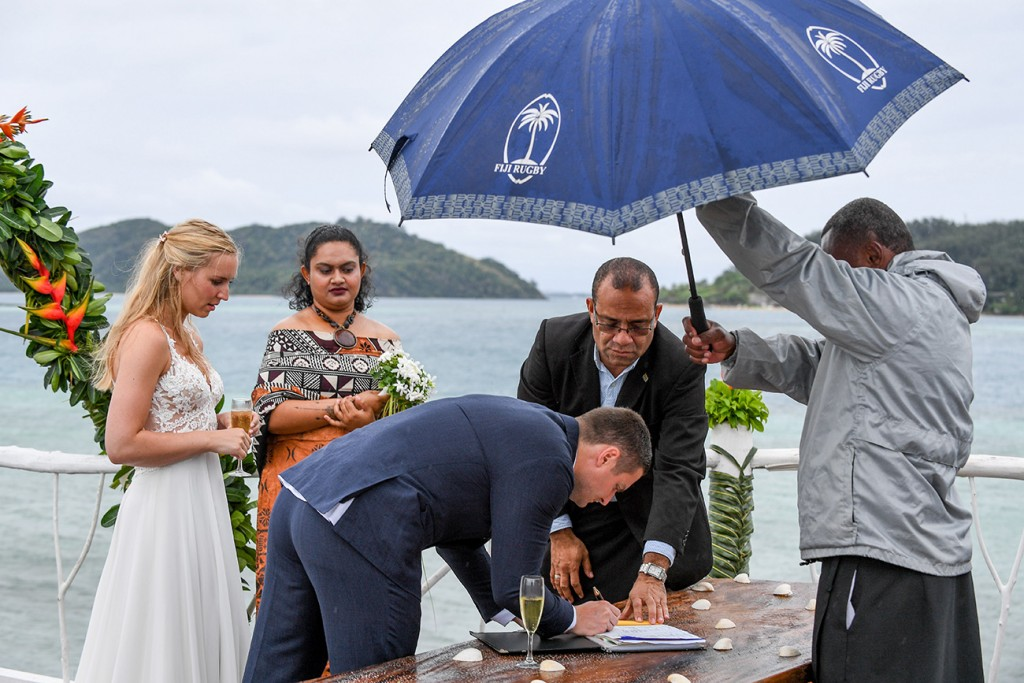 The groom signs the marriage certificate under the umbrella