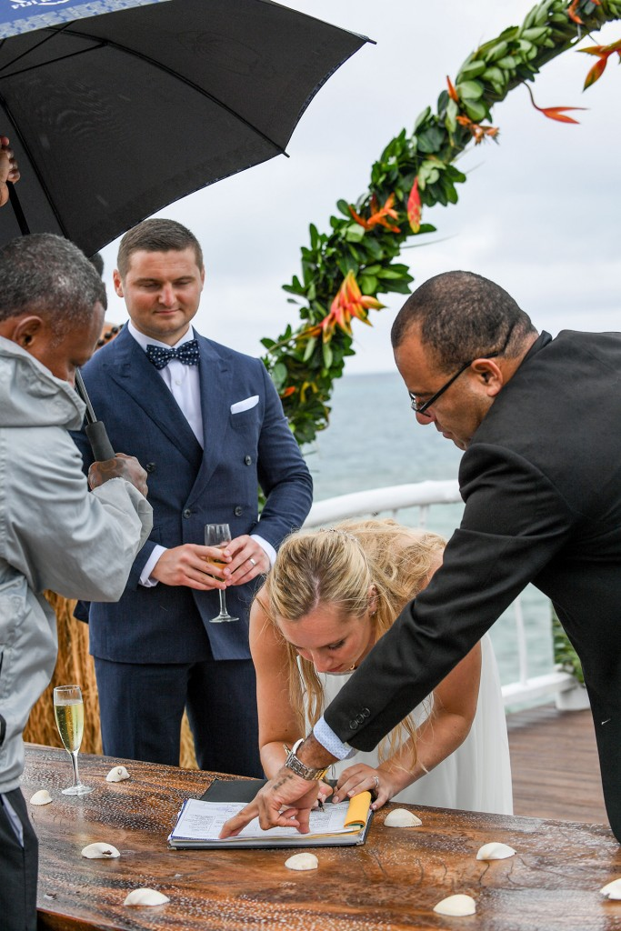 The celebrant shows the bride where to sign on the marriage certificate