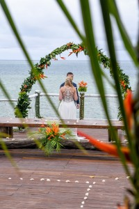 A peek through palm fronds of the newly weds at the beach view altar