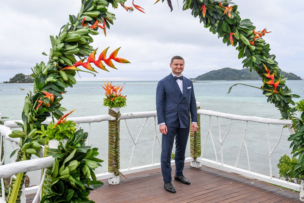 The groom poses at the altar by the Pacific ocean