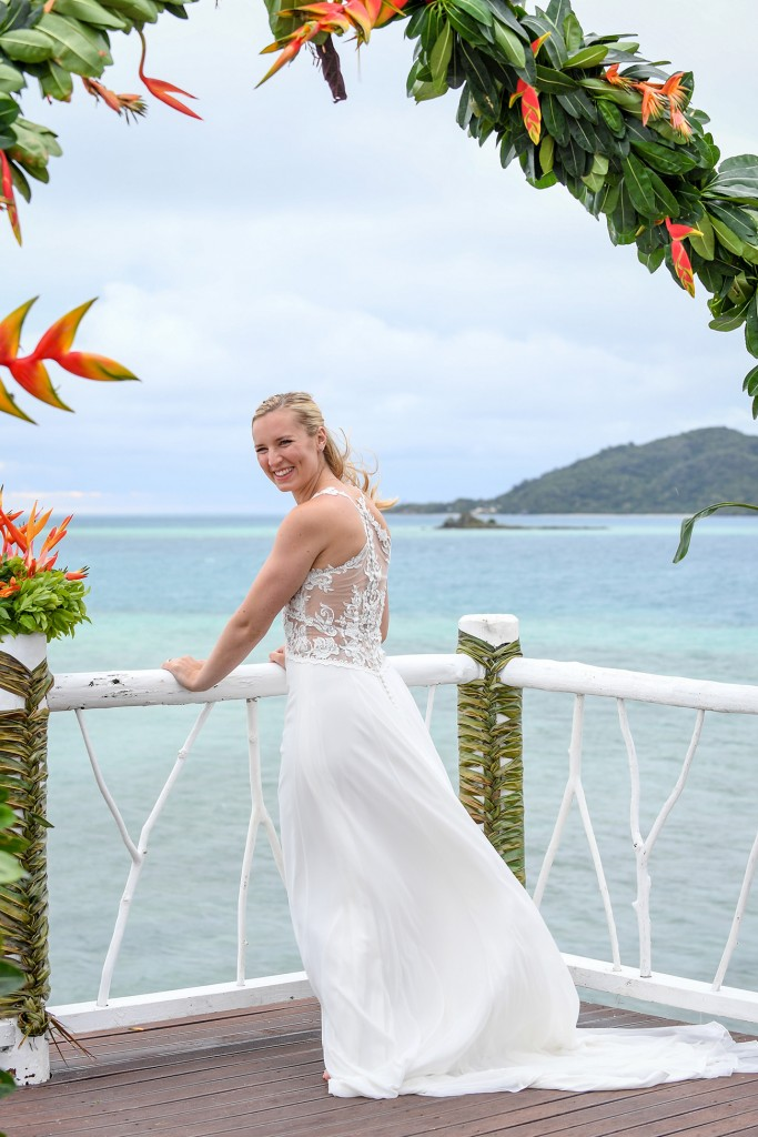 The bride poses at the altar by the Pacific ocean