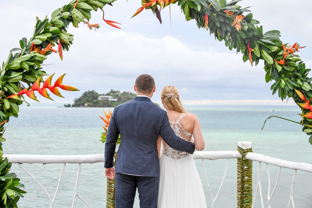 The newly weds stare into the Pacific ocean after the wedding ceremony