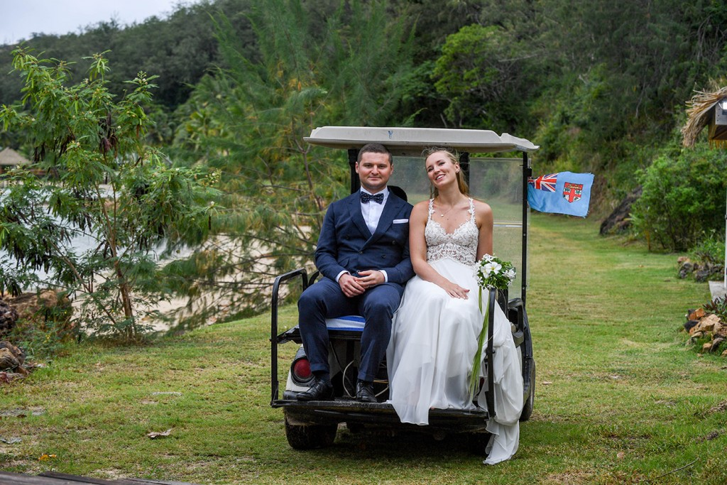 The newly weds leave in a golf cart