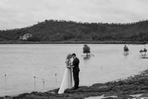 A monochrome photo of the newlyweds holding hands on the shore of the Pacific Ocean