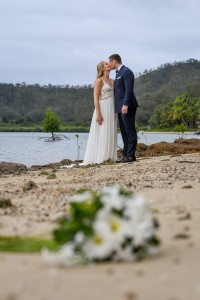 The newlyweds kiss on the shore of the Pacific