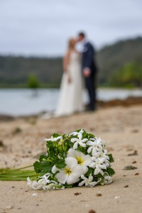 The newlyweds kiss in the background of white frangipanis