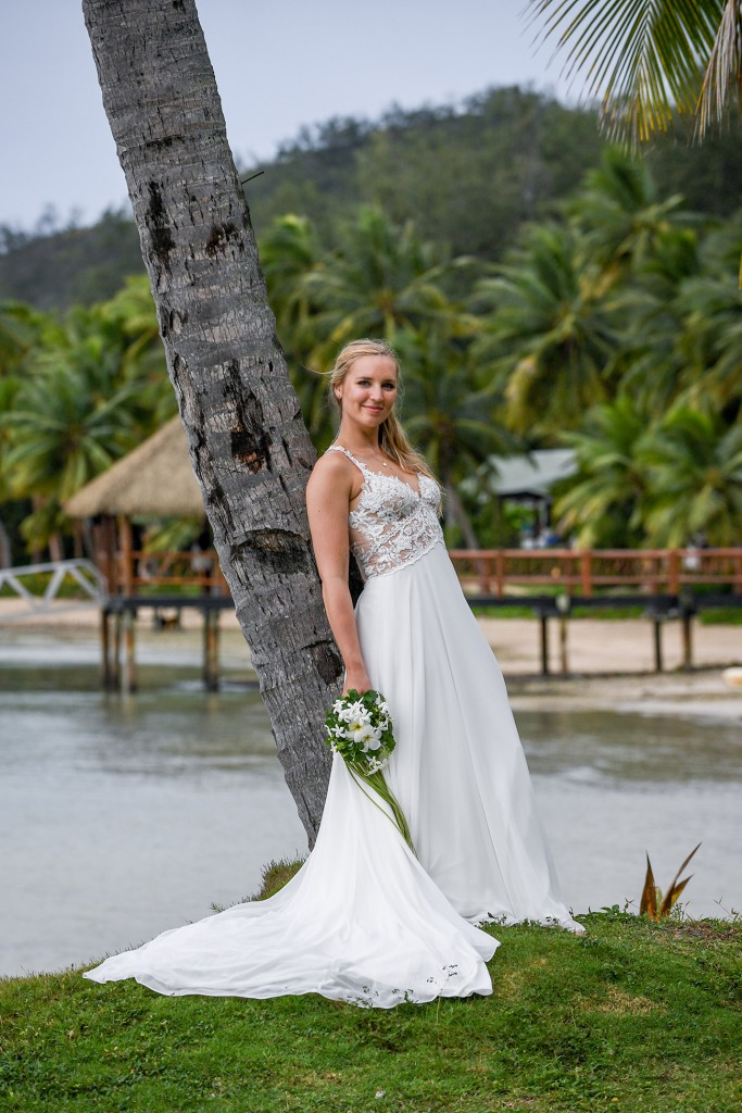 The bride leans against a towering Fiji palm tree