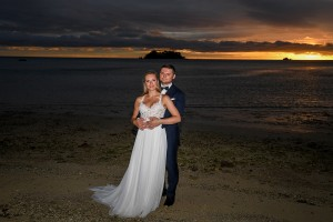 The newly weds pose with a fiery sun setting behind them
