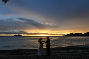A silhouette of the newlyweds dancing on the shore at sunset