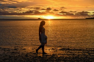 A silhouette of the bride strolling the shores of the Pacific at sunset