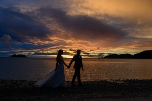 A silhouette of the newly weds strolling along the shores of the Pacific