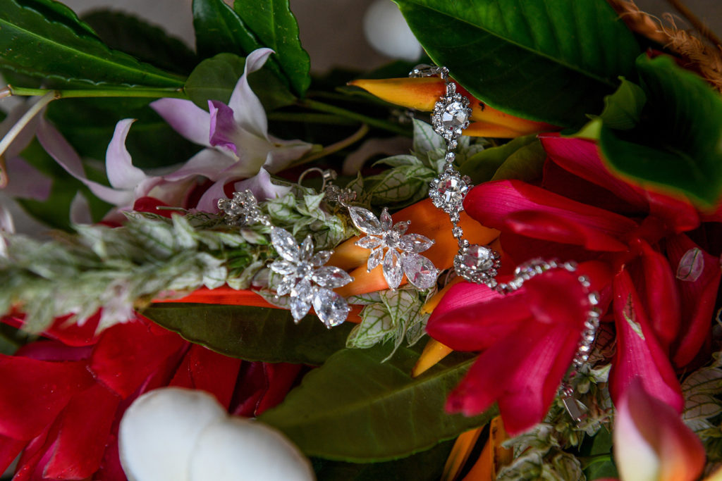 Diamond earrings are nested on the fresh flower pink ginger bouquet