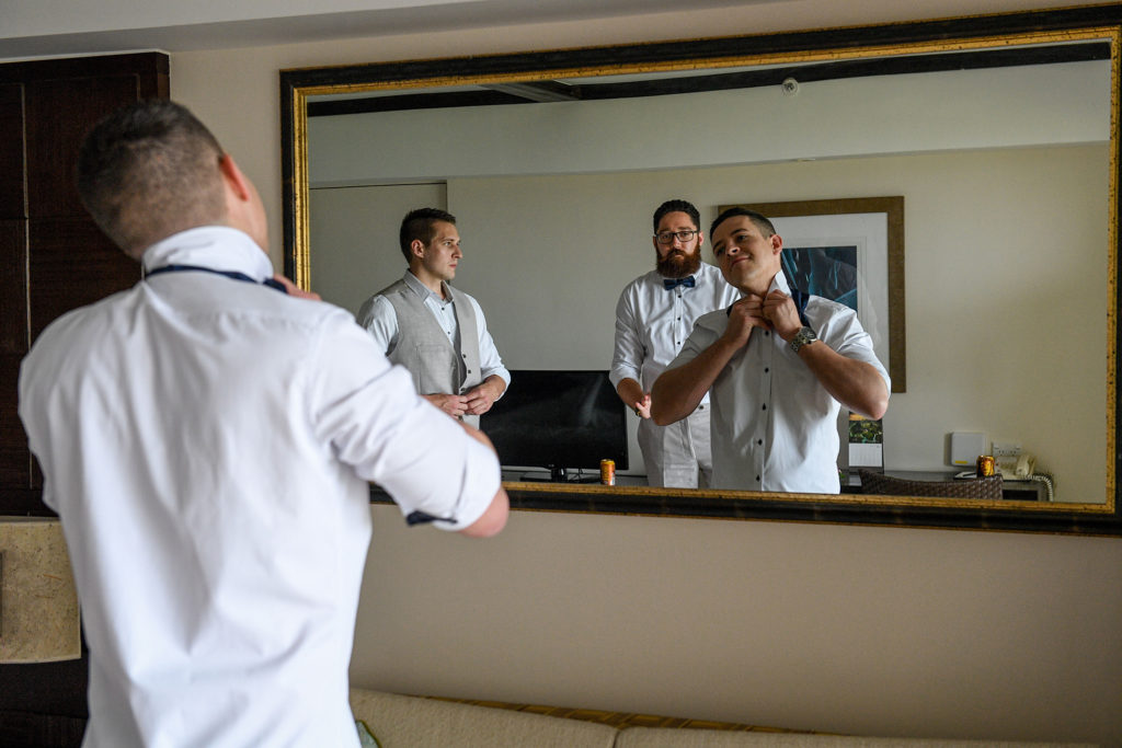A reflection of the groom getting ready at the Shangri La Fiji