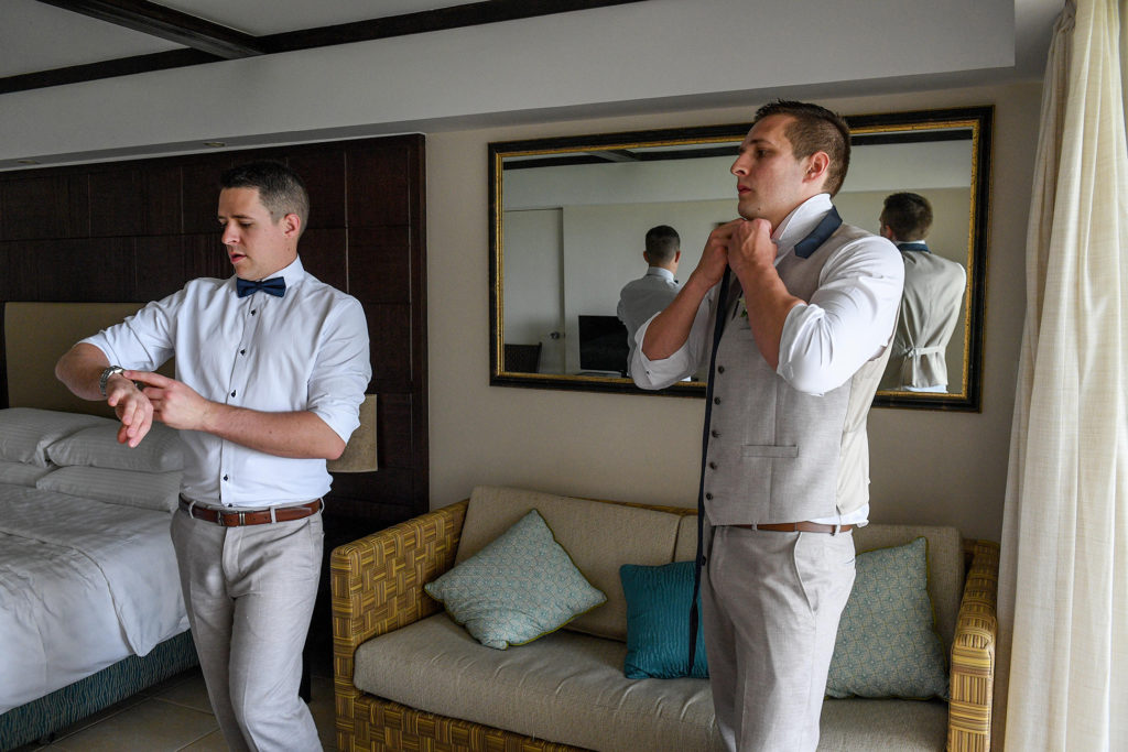The groomsmen fasten their bow ties as they prepare for the wedding