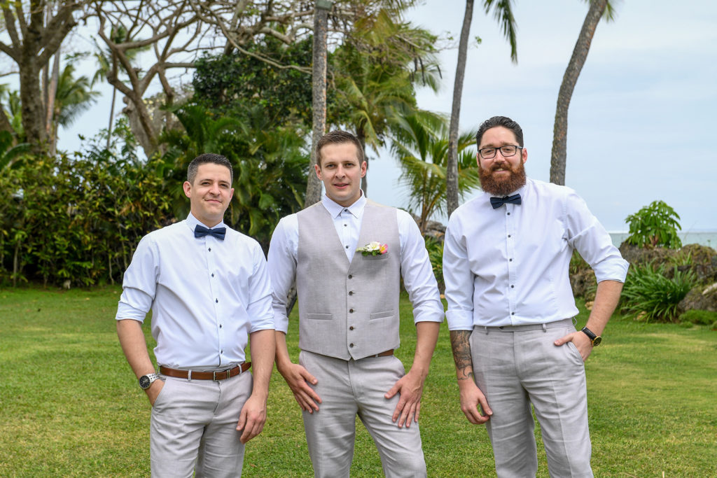 The groom and his groomsmen strike a pose with tall palm trees in the background
