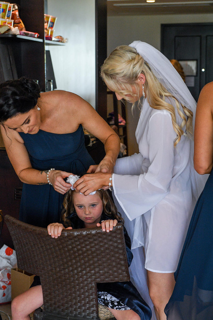The bride and bridesmaid help curl the flower girl's hair