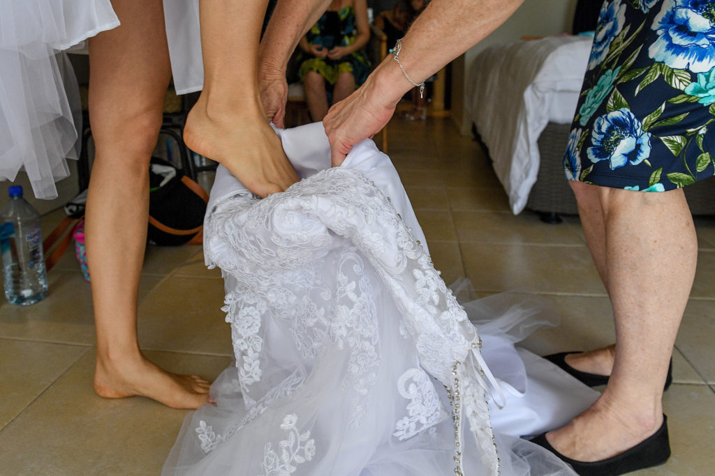 The bride steps into her stunning lace detail wedding gown