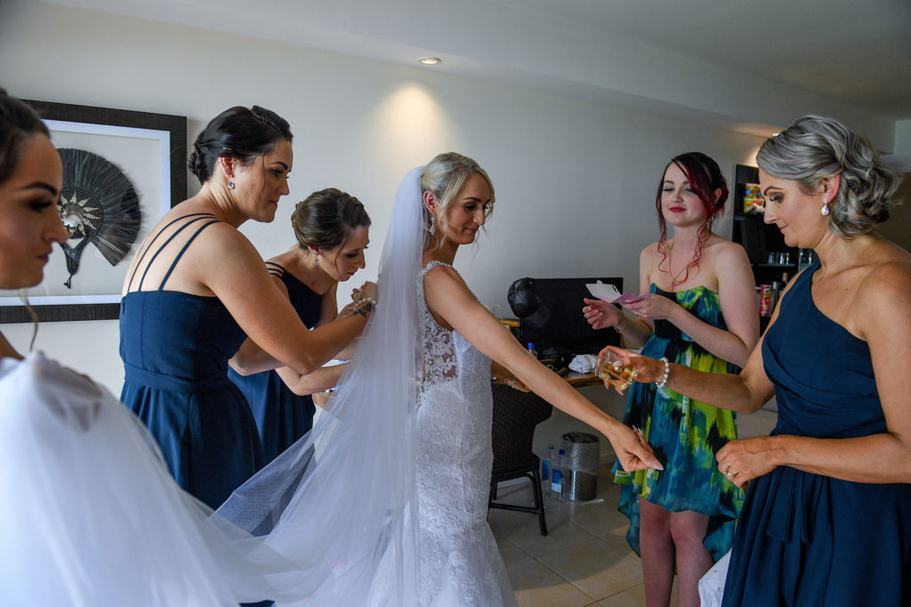 The bride shows off her stunning wedding gown to the bridesmaids