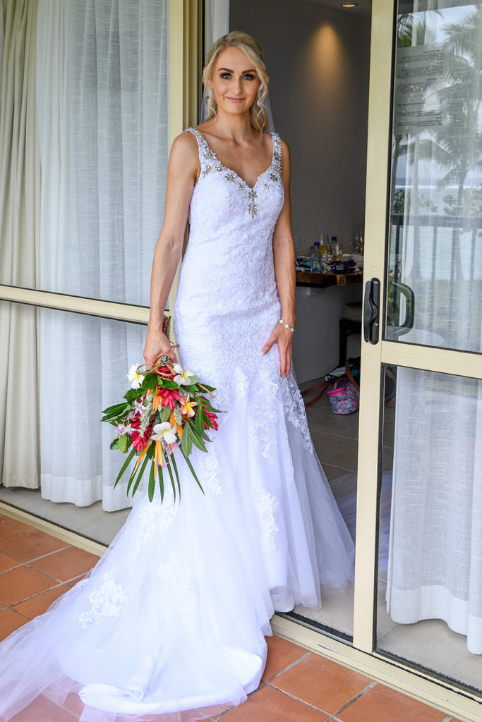 The stunning bride poses in the doorway in a brilliant white gown and fresh Fiji flower bouquet