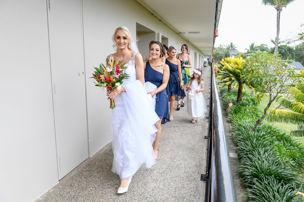 The bride and her bridesmaids form a procession as they walk out of the hotel room