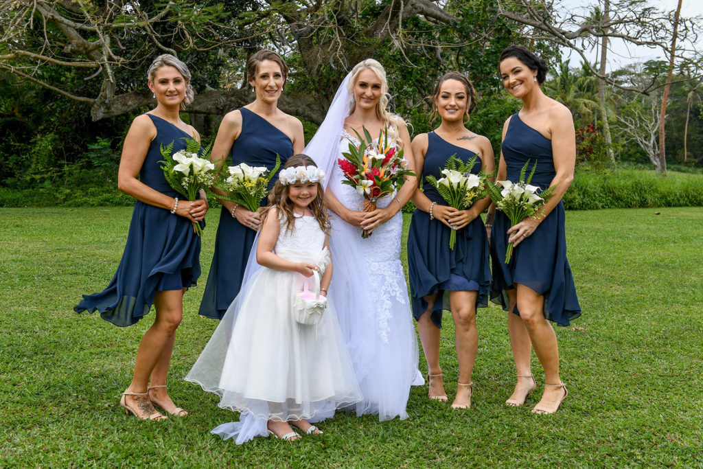 The bride poses with her bridesmaids and flower girls