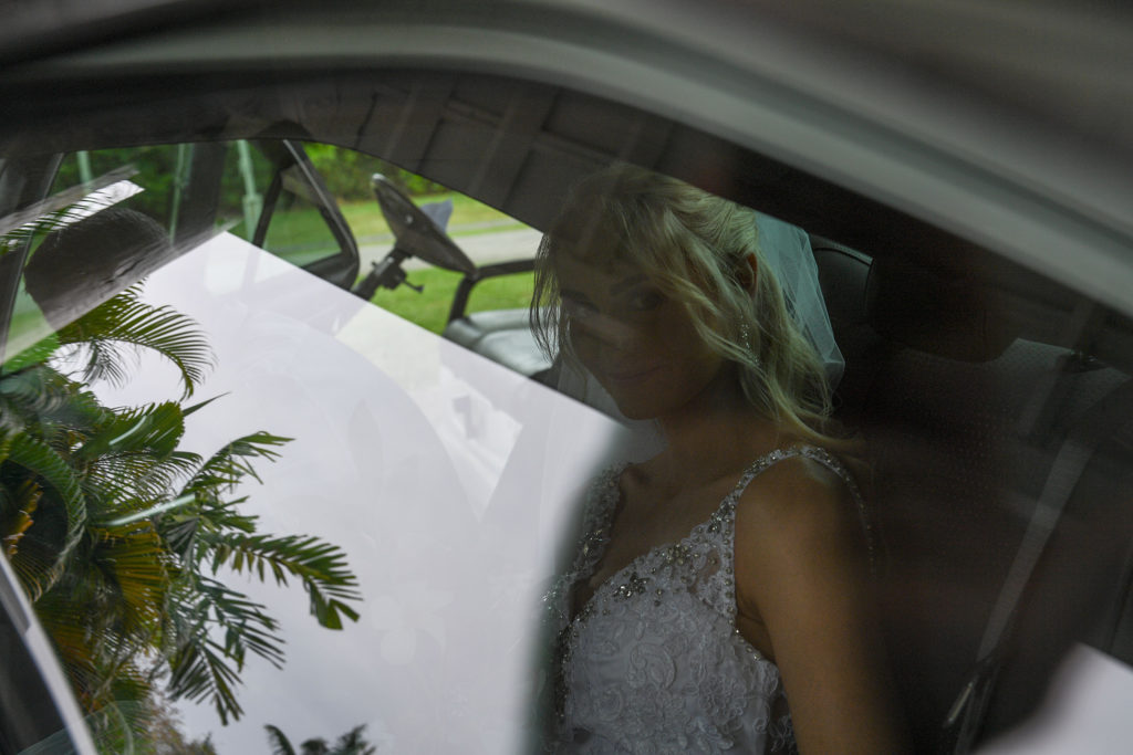 Palm trees reflect off the car window with the stunning bride in the background