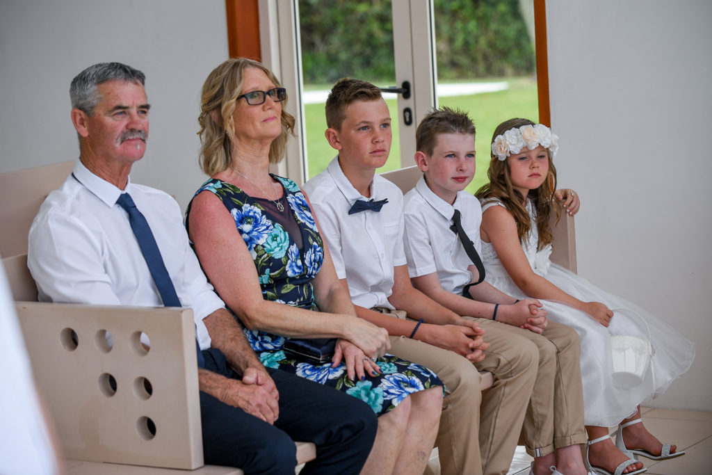 The family, best boys and flower girl watch the wedding ceremony