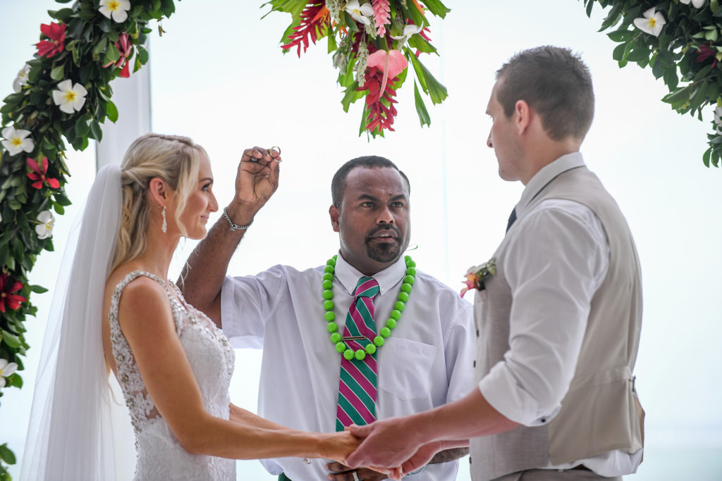 The celebrant raises the ring while presiding the wedding at the altar