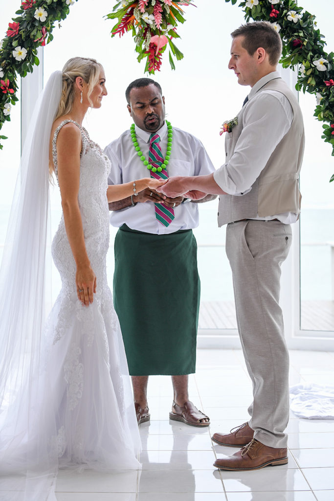 The groom slips the ring onto his bride's finger at their beach wedding in Shangri La