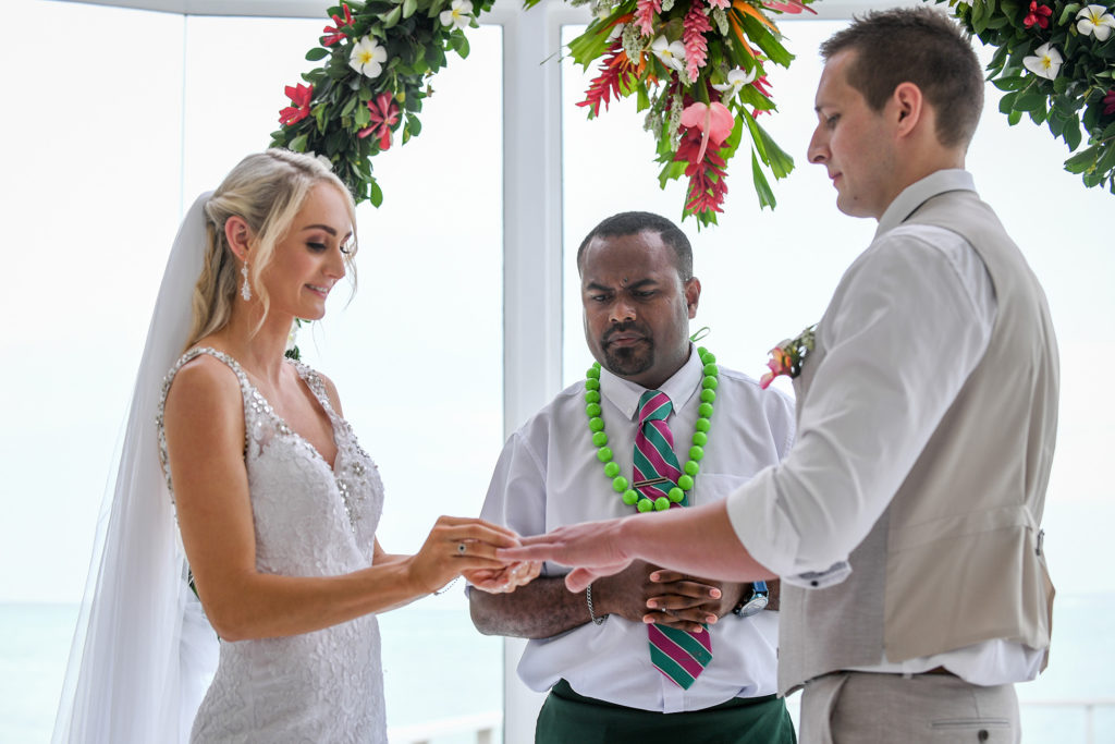 The bride slips the ring onto the groom's finger as the celebrant watches on