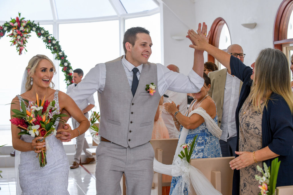 The groom high fives one of the guests as he walks down the aisle