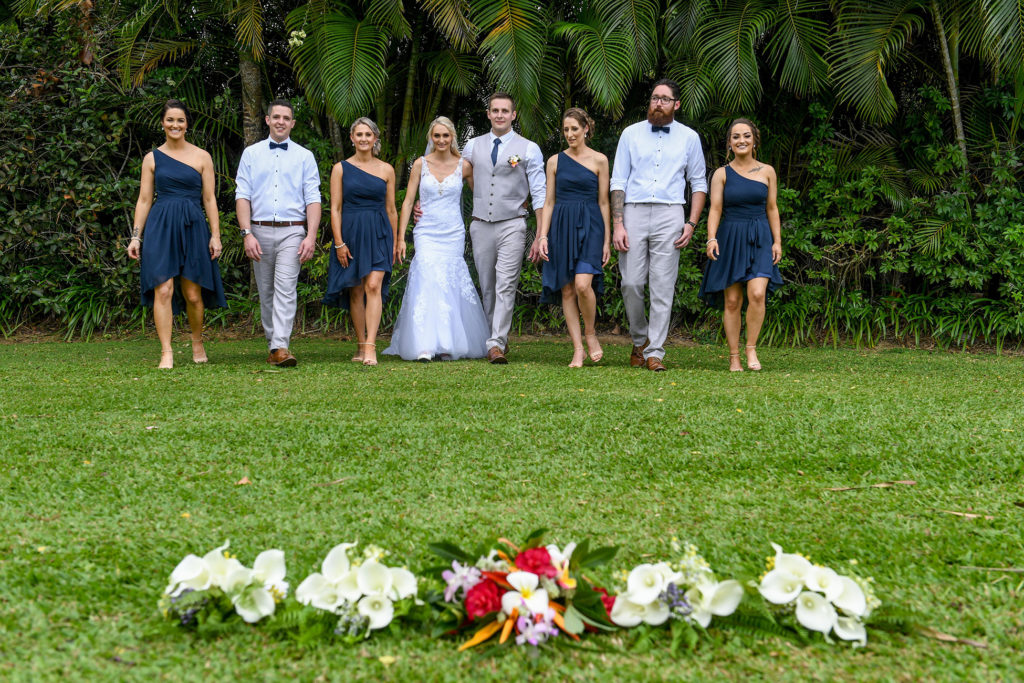 The newly weds pose with their bridal party with palm trees in the background