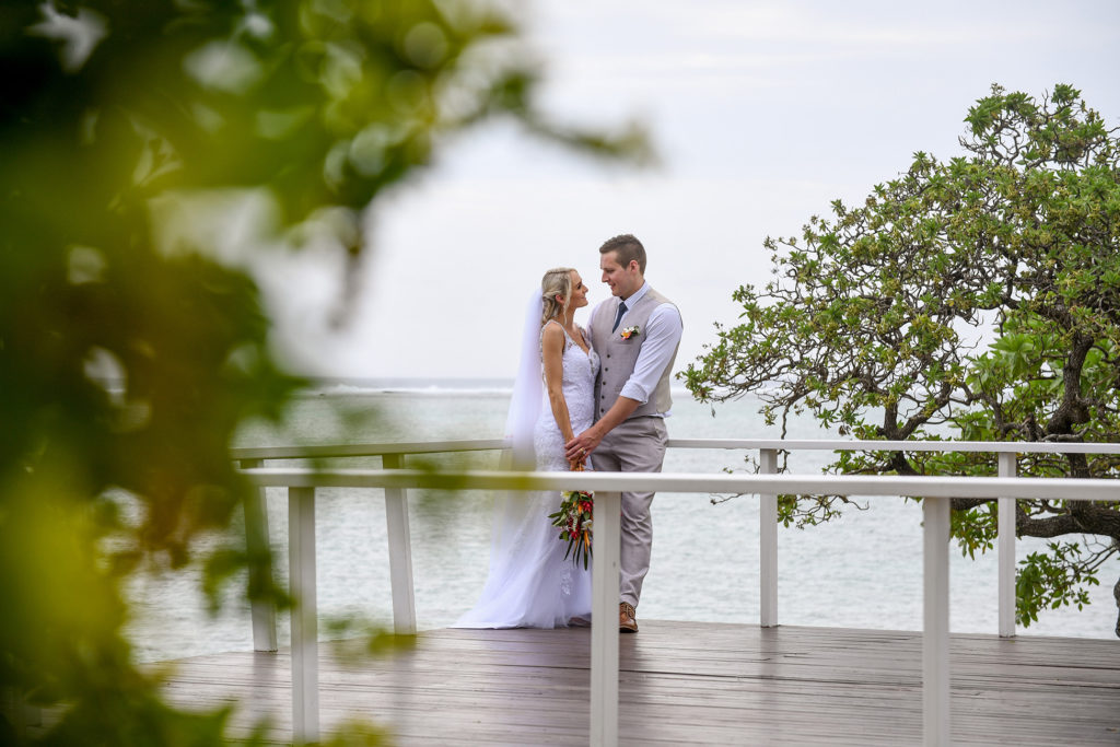 The bride and groom share an intimate moment while standing at the dock at Shangri La