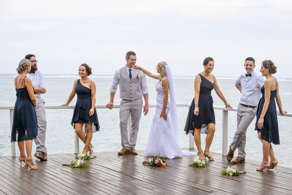 The bridal party and the newly weds hang out on a dock
