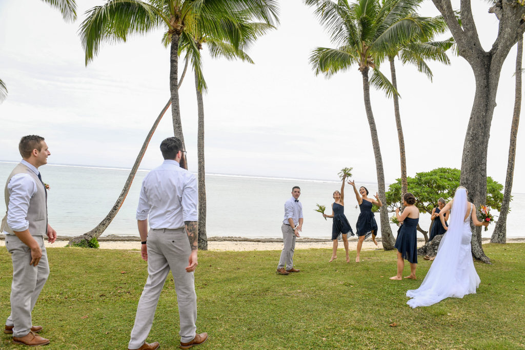 The bridal party plays and has fun under the towering Fiji palm