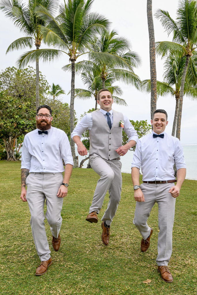 The groom jumps with his groomsmen under towering Fiji palm trees