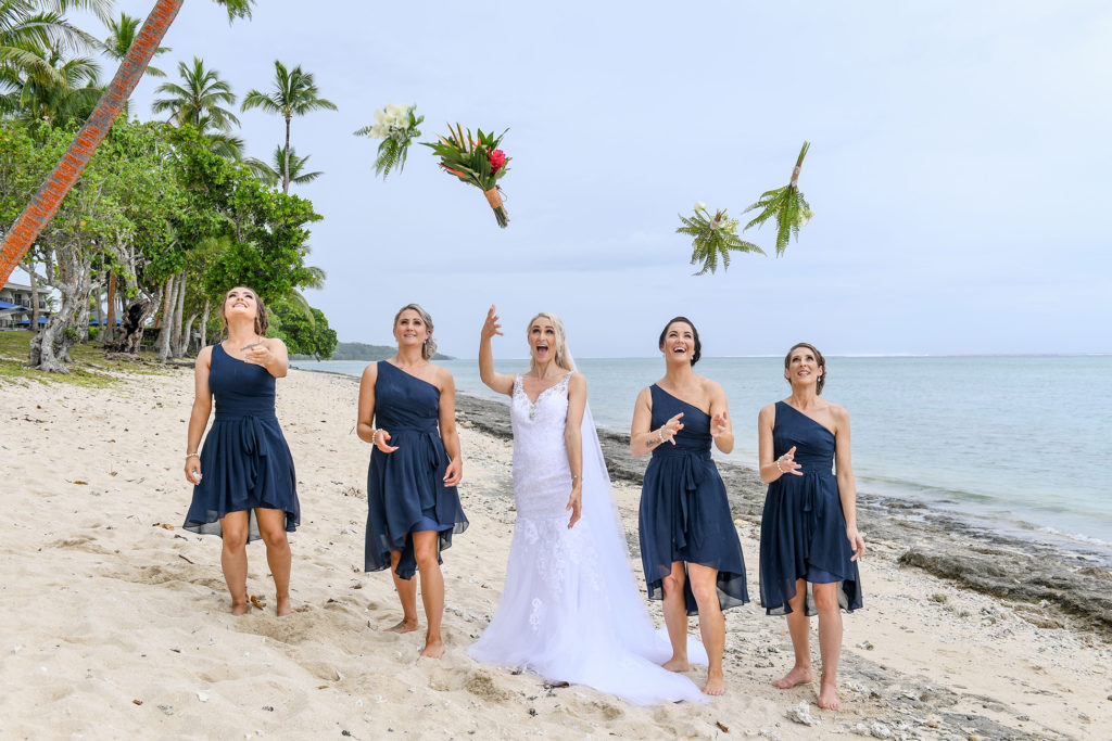 The bride and her bridesmaids toss their bouquets as they walk down the beach at Shangri La Fiji