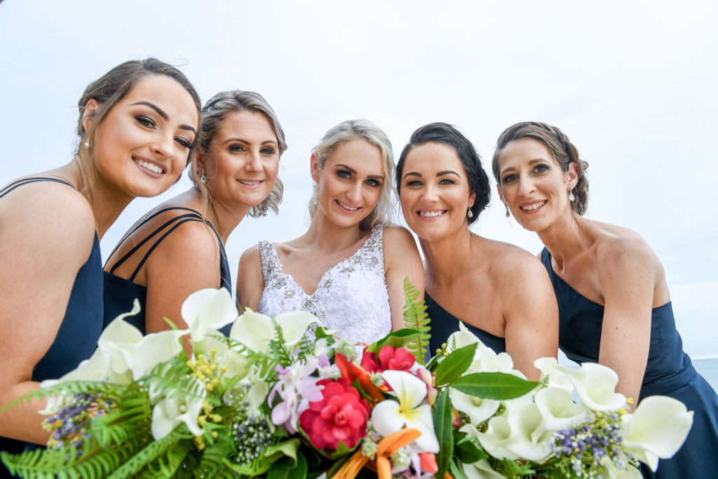 Smiling bride and bridesmaids pose with their bouquets