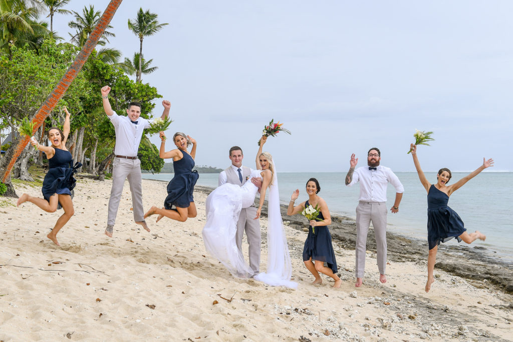 The newly weds celebrate on the beach with their bridal party