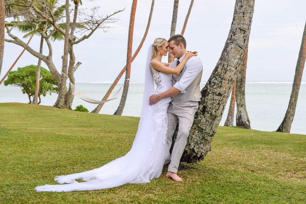 The newly weds share an intimate moment cuddling against a leaning palm tree