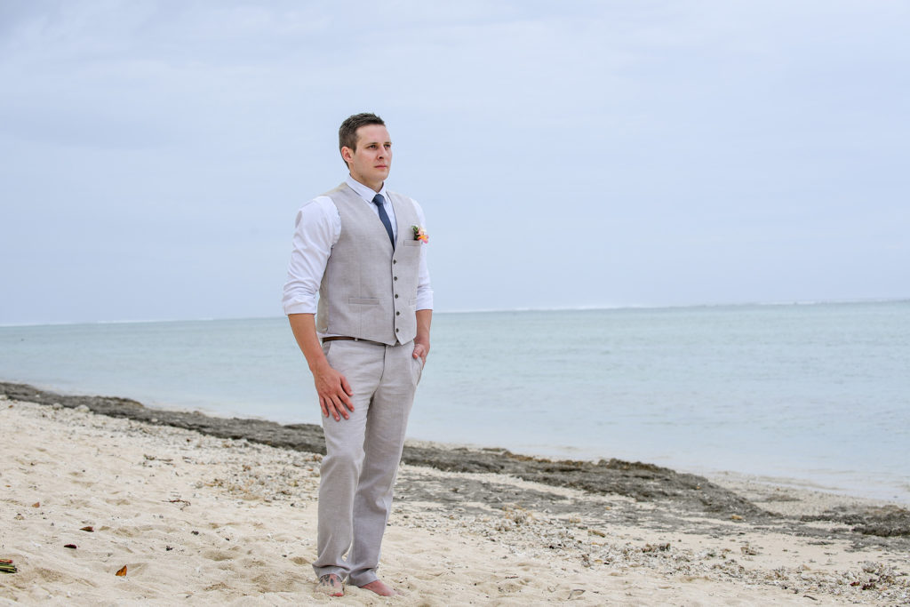 The groom stands alert on the beach