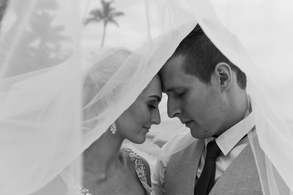 A monochrome portrait of the newly weds posing under the bride's veil