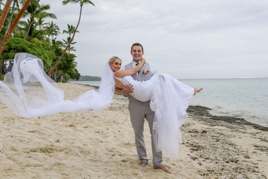 The groom carries his bride on the beach with her veil flowing behind them