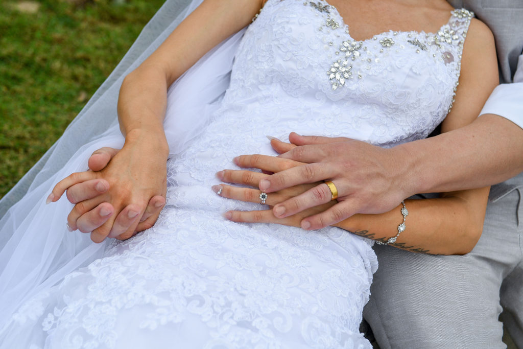 An portrait of the bride and groom getting cosy with closeup on their wedding bands